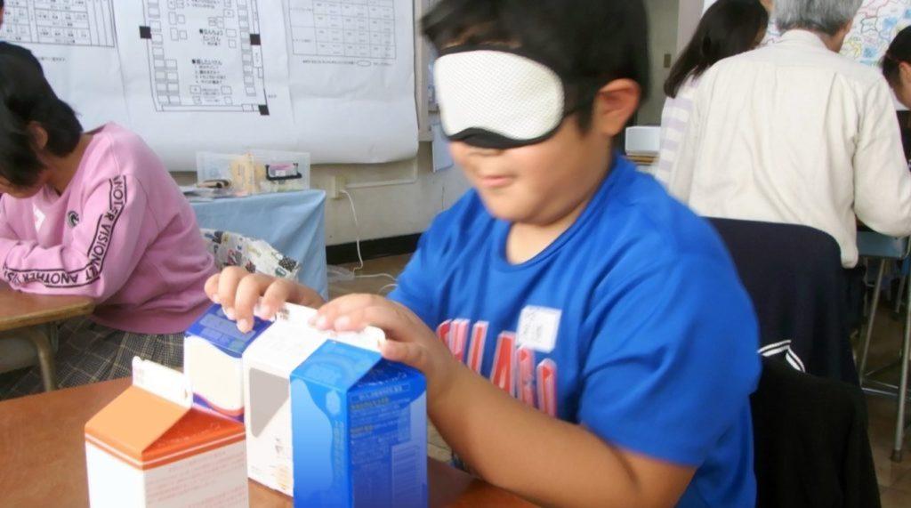 図5、アイマスクをつけて牛乳パックを探す体験